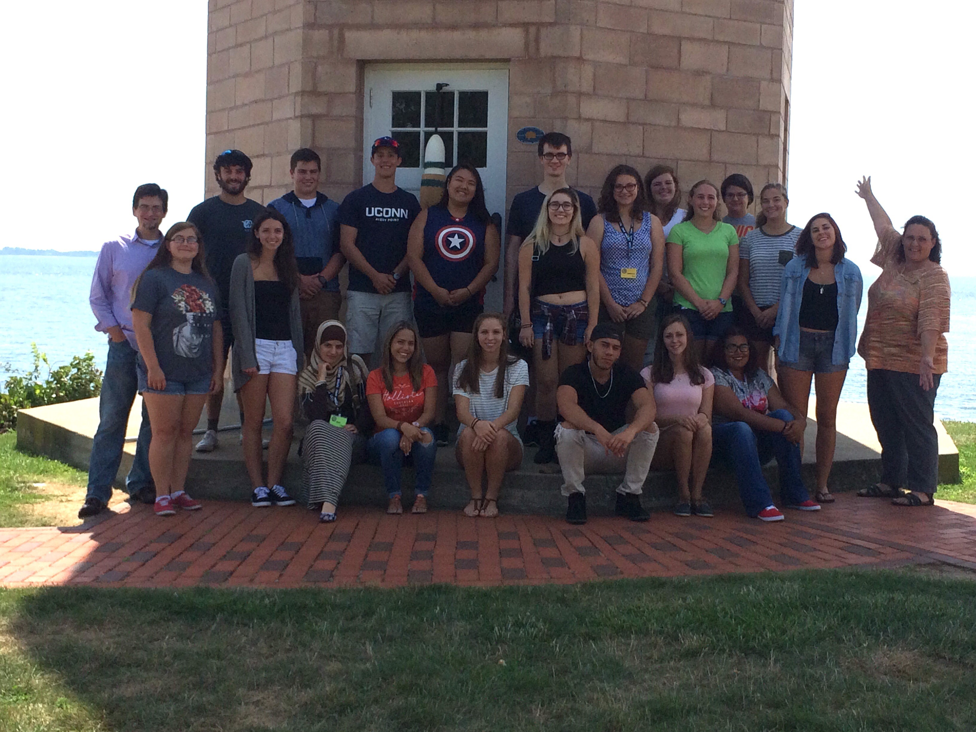 A group picture of the APAC staff in front of the Avery point Lighthouse